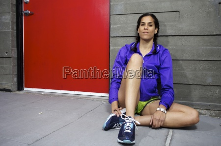 a female runner rests by a