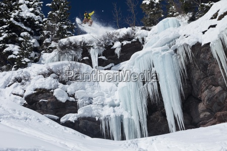 a snowboarder jumps off an ice