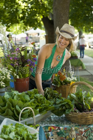 a young woman looks over produce