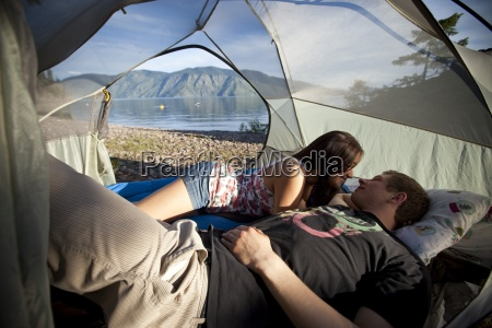 a young couple camping talk in