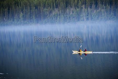 a couple paddles a kayak through
