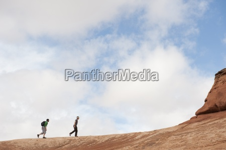 two young men hiking in arches