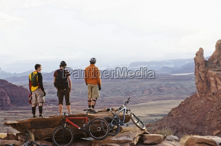 three young men overlook a canyon