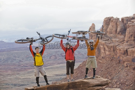 three young men hold their bikes