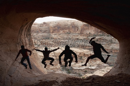 four young men jumping are silloutted