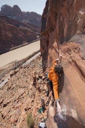 a young man rock climbs near