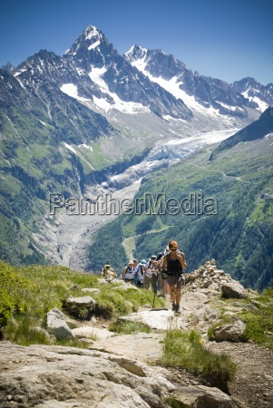 hikers trek up a hill as
