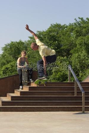 two male skateboarders doing tricks off