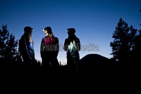 three women talk while enjoying a