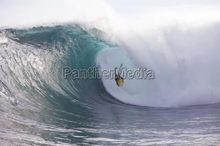 un hombre bodyboarding una ola enorme