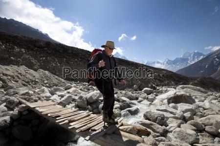 a trekker carefully crosses a wooden