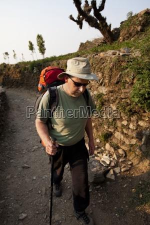 a trekker puts his head down