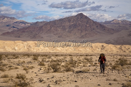 a young man backpacks through the
