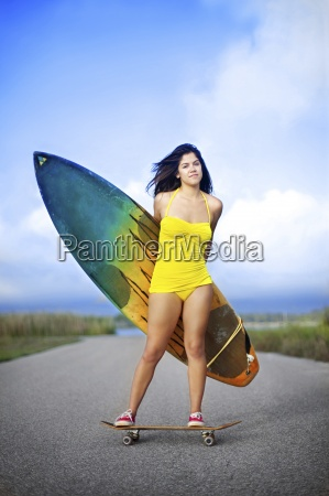 young woman wearing yellow swimsuit standing