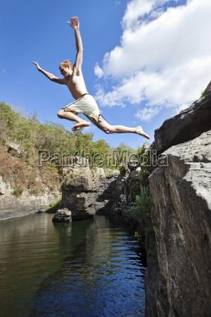 young man jumps off rock cliffs