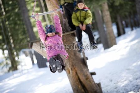 a boy and girl zipline over