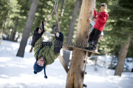 two brothers zipline over the snow