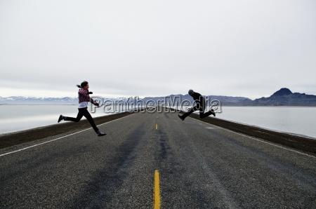 a couple jump on a long