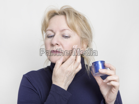 elderly woman with face cream