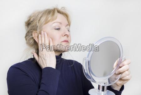 elderly woman looks in mirror