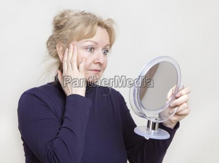 senior looks in mirror