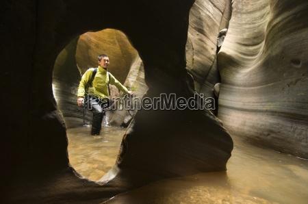 an asian man canyoneering through a