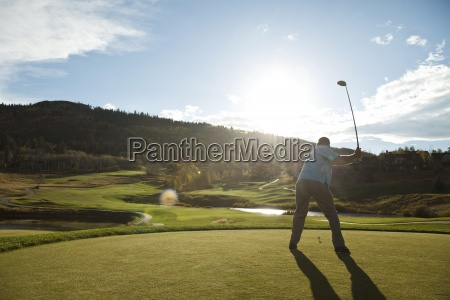 a golfer drives at sunset in
