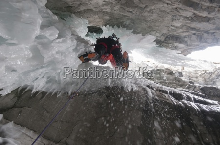 a man ice climbing in marble