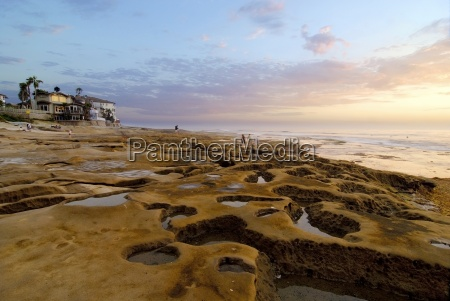 people wander through tide pools at