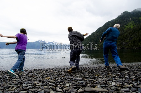 three men have a rock skipping