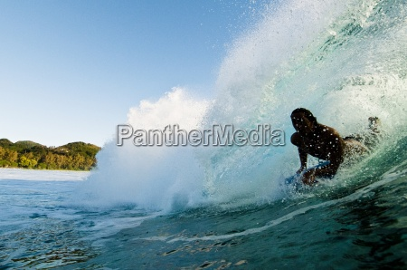 bodyboarding pulling into a barrelling wave