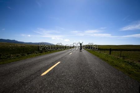 a male cyclist raises his arms