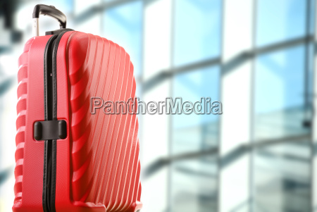 red plastic travel suitcase in the