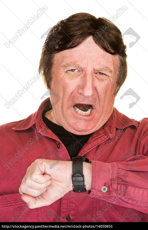 yawning, man, looking, at, watch - 14050855
