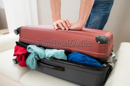 person hand trying to close suitcase