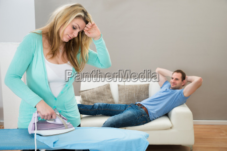 tired, woman, ironing, while, man, on - 14062499