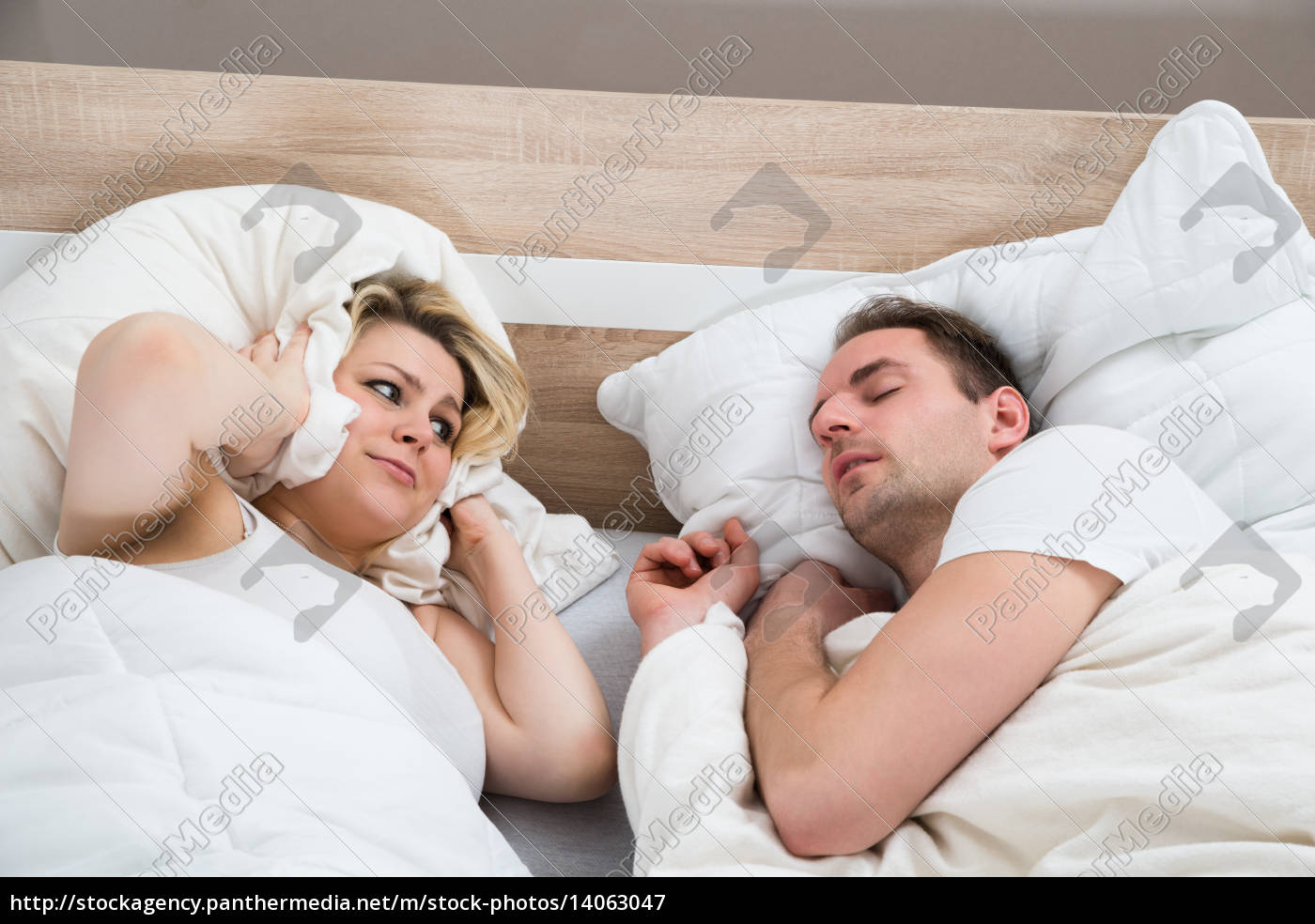 woman, covering, ears, while, man, snoring - 14063047
