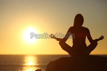 woman meditating and practicing yoga watching