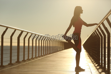 woman silhouette exercising stretching on a