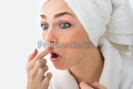 shocked woman looking at pimple on