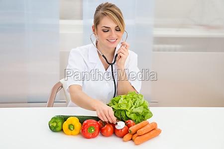 female, dietician, examining, vegetables - 14083649