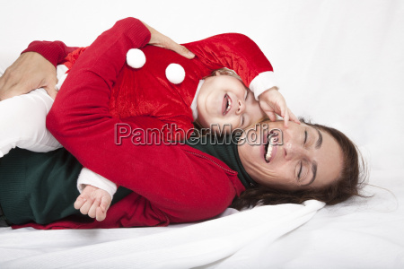 baby santa claus laughing with mother