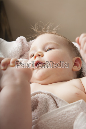 face of baby lying on towel