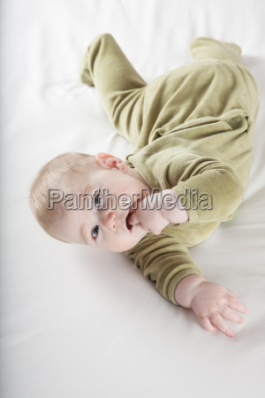 baby, lying, twisted, looking, at, camera - 14089845