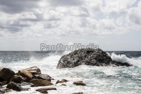 liguria rocky cliff on rough sea