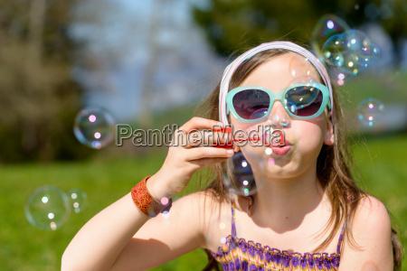 a, little, girl, making, soap, bubbles - 14100039