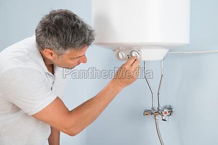 man adjusting temperature of electric boiler