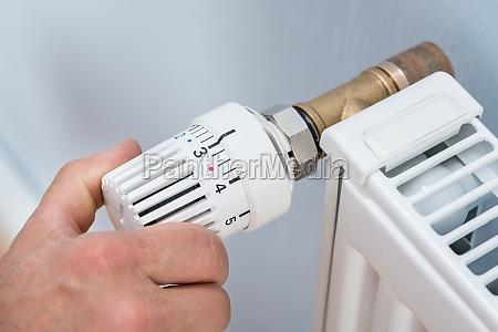 person adjusting temperature of radiator thermostat