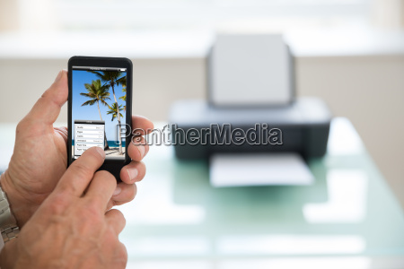 person using cellphone for printing photo