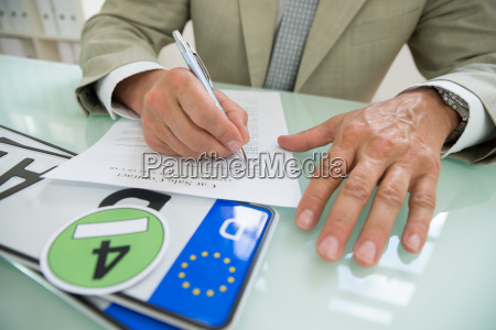 businessman filling car sale contract